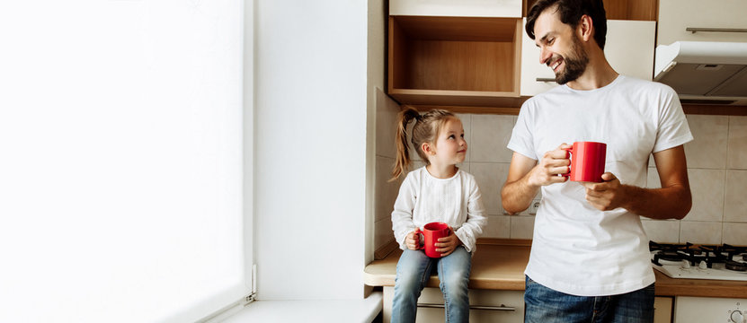 Parenthood. Family. Love. Dad and his little daughter are holding red cups, looking at each other and smiling. In the kitchen at home