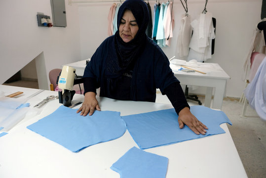 A woman works in a sewing workshop supervised by a charity to help widows, divorcees and needy in Benghazi