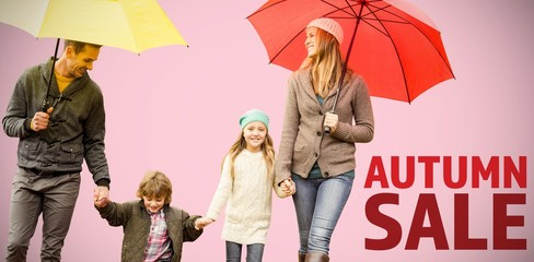 Composite image of  smiling young family under umbrella