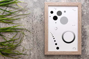 Wooden frame with graphics in circles on the background of old concrete and green grass