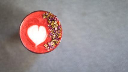 Fashionable strawberry latte, latte art and flower petals on foam, grey background.