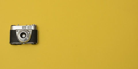 old retro camera on yellow background composition