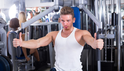 well trained man using pec deck gym machinery indoors