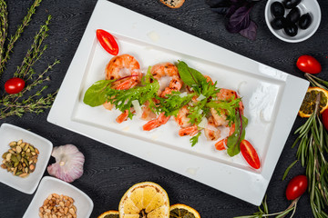 salad of fried shrimp with herbs and tomatoes on a white plate