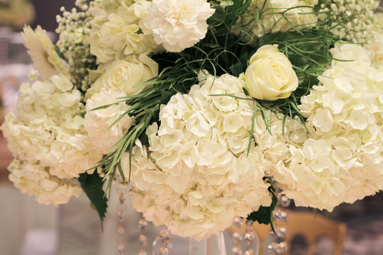 Wedding table flower decoration close up. Hydrangea, roses and orchid bouquet. Glamorous Event, celebration