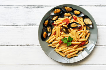 Penne pasta with mussels on a white wooden rustic table. Top view, copy space.