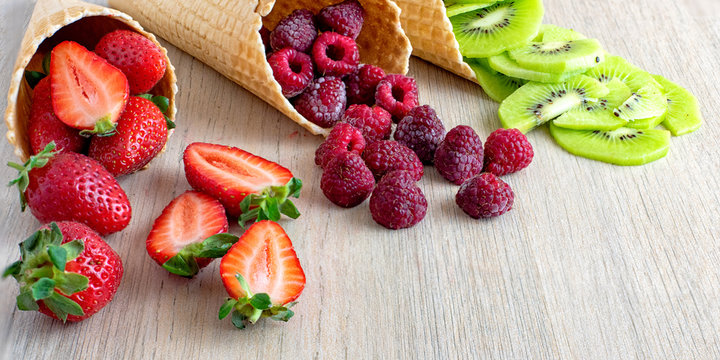 Strawberry, kiwi, raspberry in waffle cones on light wooden background. Close up