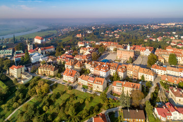 Aerial skyline panorama of Sandomierz old city, Poland, in sunrise light. Old town with market square, Gothic city hall, medieval castle on the left and Vistula River in morning fog in the background