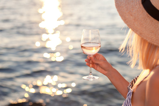 Girl holds wineglass with white wine in hand on beach at summer background of sunset sea or ocean. Blond beautiful woman is straw hat is relaxing, drinking, traveling and enjoying life in vacation.