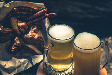 Glass of light beer against background of green trees outdoor. Snack sausage, smoked chicken wings, vintage toning picture