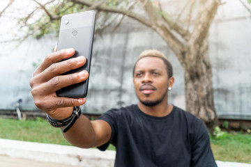 Close up of attractive dark-skinned man making selfie on mobile phone.