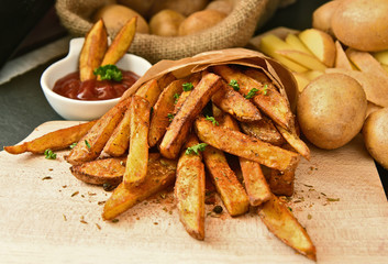 Homemade Crispy Seasoned French Fries..French fries  with spicy seasoning in brown paper bag on wooden broad.