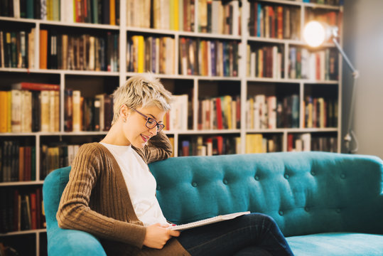 Picture of cute young girl sitting in a book store and reading book. Having some time for her self . Reading book and drinking coffee.