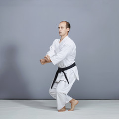A young athlete with a black belt does formal karate exercises on a gray background