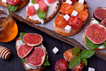 Assortment of bruschettas with figs, watermelon, cherry tomatoes, cheese and honey
