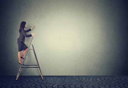 Businesswoman climbing ladder of career