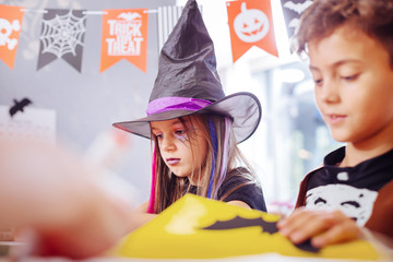 Halloween pictures. Cute good-looking brother and sister feeling busy while drawing Halloween pictures together