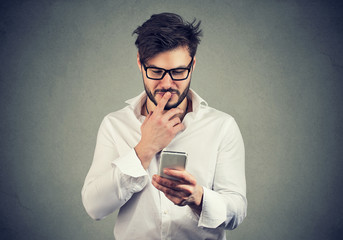 puzzled man thinking what to reply to received text message on cell phone
