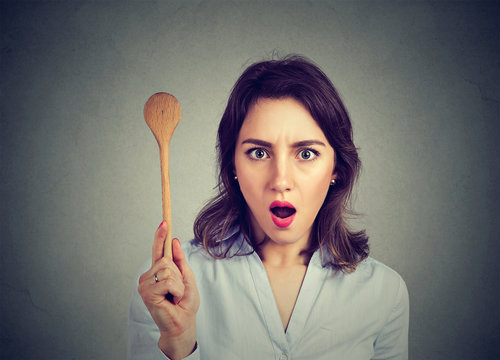Shocked woman with cooking spoon