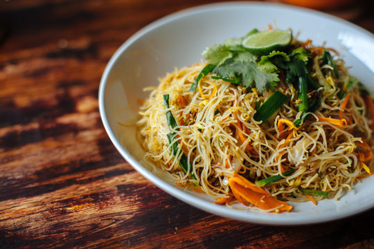 Healthy Vegetarian vegan menu Delicious Singapore style Stir fried rice noodles with carrot orange smoothies on wooden table in cafe