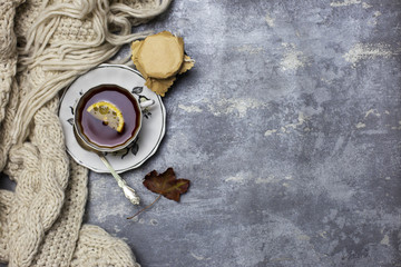 Cup with black tea and lemon and saucer, spoon, jelly in jar, maple leaves and knitted scarf near, an gray background
