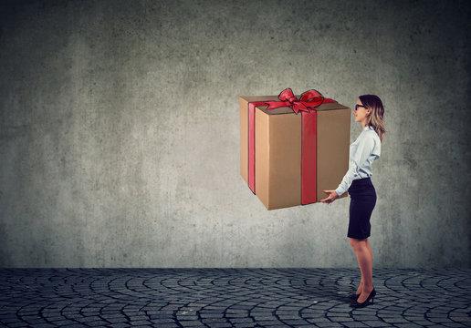 Woman holding a big present gift box