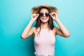 Portrait of pretty woman in sunglasses and hat over blue colorful. Summer concept.