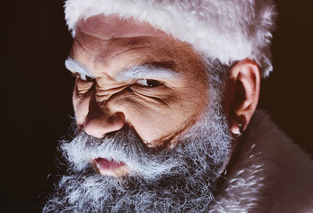 Angry Santa furiously grimaces against a dark background