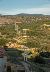Electricity lines transmission carrying power across the countryside in mountain regions