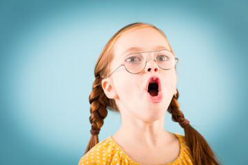 Singing Little Girl with Glasses, Isolated on Teal