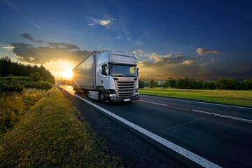 Fotobehang - White trucks arriving on the asphalt road in rural landscape in the rays of the sunset