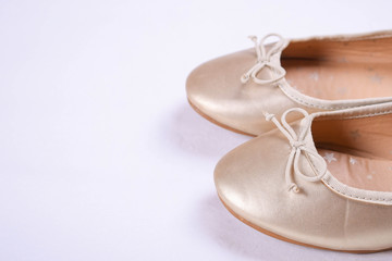 Kids shoes of gold colour.Moccasins for little princess