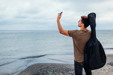 Young man with acoustic guitar taking selfie using phone on cloudy beach