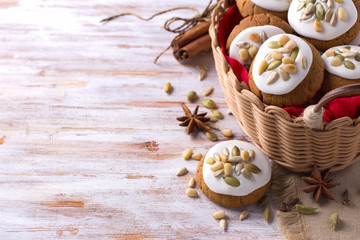 Fragrant Christmas gingerbread with glaze, nuts and seeds in a basket on a wooden background, free space, closeup, horizontal