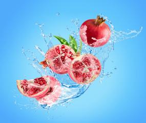 Fototapete - pomegranates in water splash on a blue background