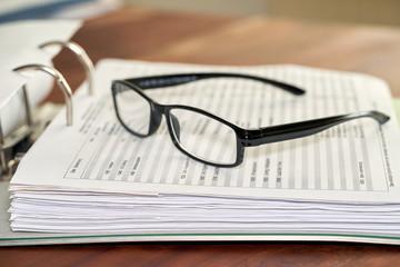 Brille auf einem Aktenordner in einem Büro