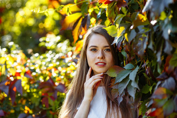 Autumn concert. Portrait of a young positive girl with long blond hair and a white t-shirt on the background of bright red and yellow leaves. Cute model openly looks at the camera. Close up