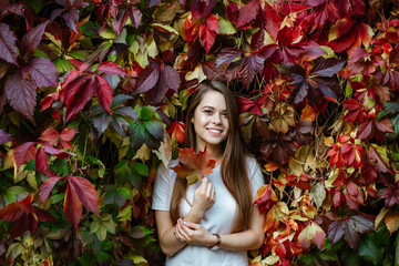 Autumn concert. Portrait of a young positive girl with long hair and a white t-shirt on the background of bright red leaves. A pretty model looks into the camera and holds a maple leaf in her hands