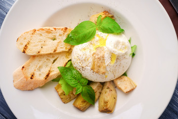 burrata cheese with artichokes and Basil and a white plate on wood table, top view