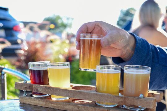 Man sampling beer at an outdoor beer garden, hands only