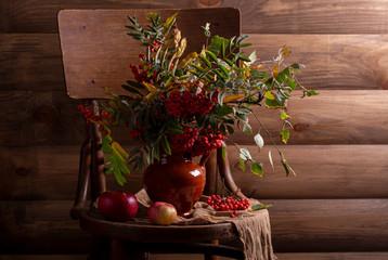 ветка рябины с красными яблоками на стуле