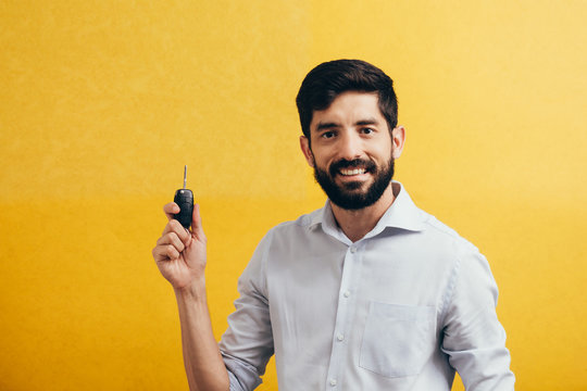 Portrait of young man smiling and holding car keys. Isolated yellow background