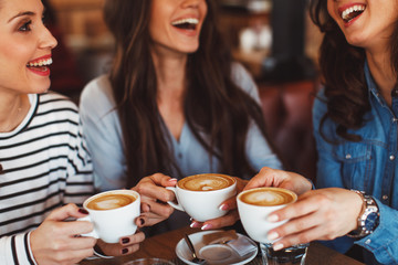 Three young women enjoy coffee at a coffee shop
