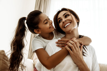 Family. Love. Mom and daughter are hugging, looking at each other and smiling while sitting on couch at home
