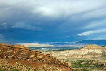 Afternoon light on the steep, sloping bluffs of the eastern side of Colorado National Monument, with the town of Grand Junction and distant mountains, as seen from Rim Rock Drive
