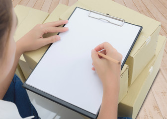 courier making notes in delivery receipt among parcels on boxes