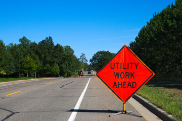 Utility Work Ahead sign with service vehicle down the street Wall mural