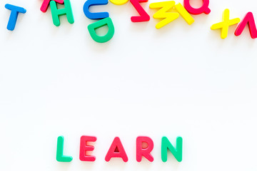 Children learn read concept. Word learn written by plastic letters on white background top view copy space