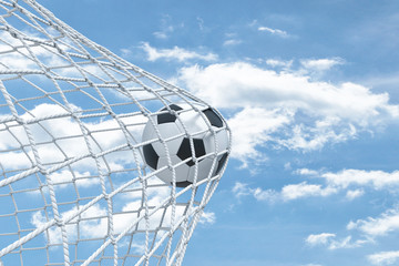 Fototapeta 3d rendering of a football ball caught in a white net from the gates on a sky background.