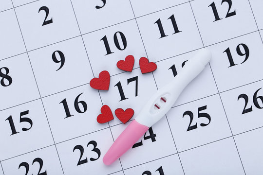 Pregnancy test on paper calendar with red hearts